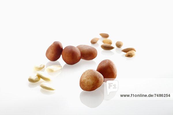 Marzipan-Kartoffeln mit Mandeln auf weißem Grund