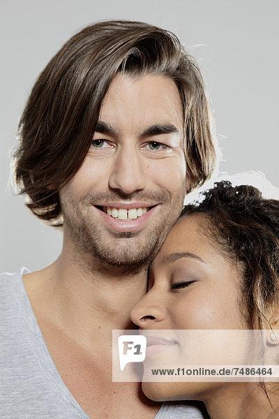 Nahaufnahme des Paares vor grauem Hintergrund  lächelnd