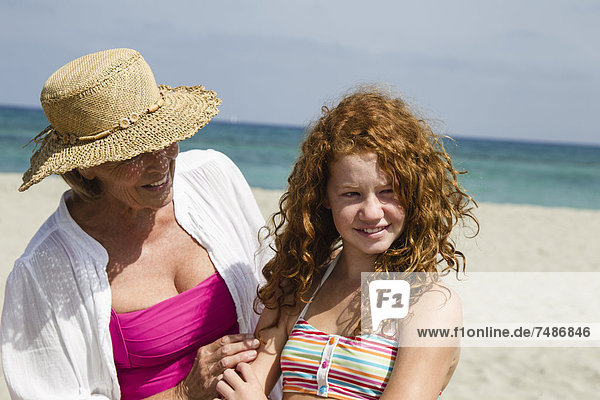 Spain  Grandmother and granddaughter at beach  smiling
