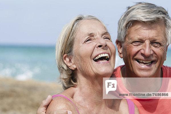 Spanien  Seniorenpaar am Strand  lächelnd