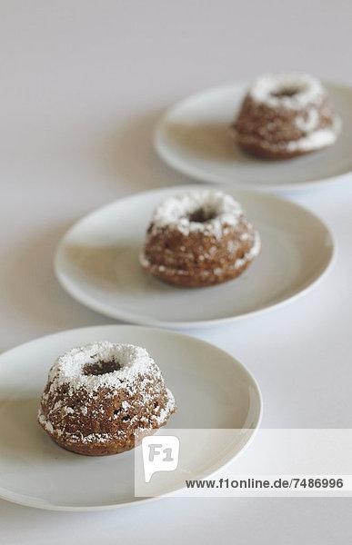 Miniaturkuchen mit Puderzucker auf Teller