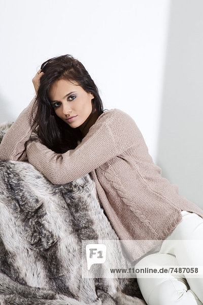 Young woman sitting on fur blanket  portrait