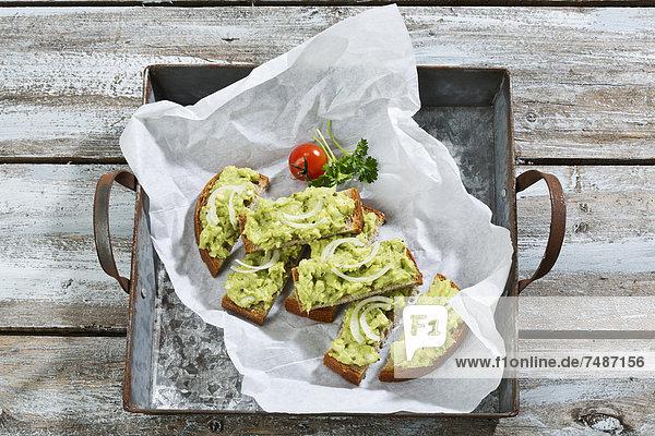 Brotscheiben mit Avocado-Aufstrich auf dem Tablett  Nahaufnahme