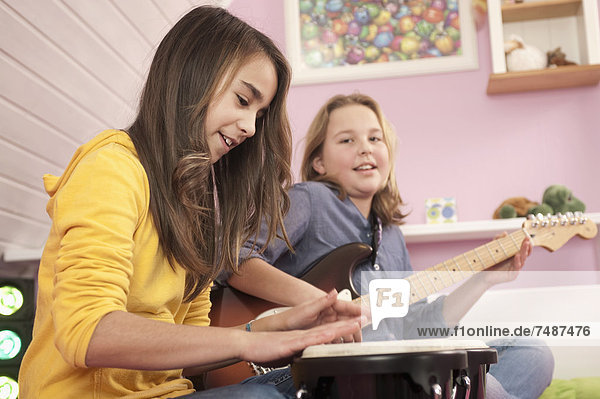 Girls playing guitar and drums  smiling