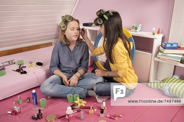 Girls with hair rollers applying make up  smiling