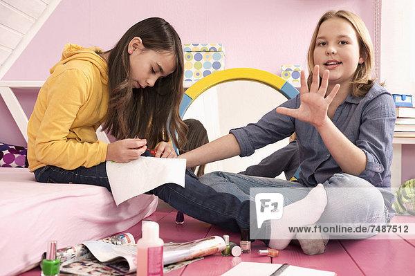 Girls applying nail varnish  smiling