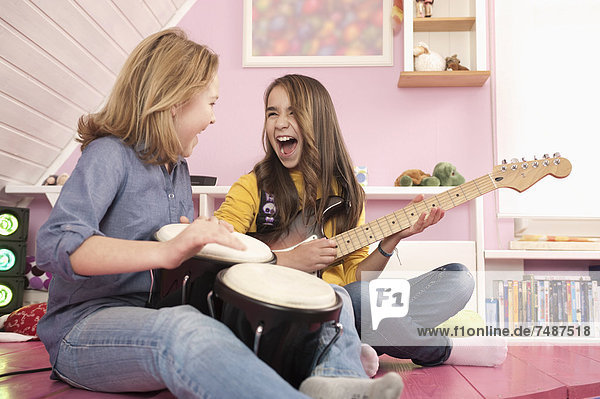 Girls playing guitar and drums  laughing