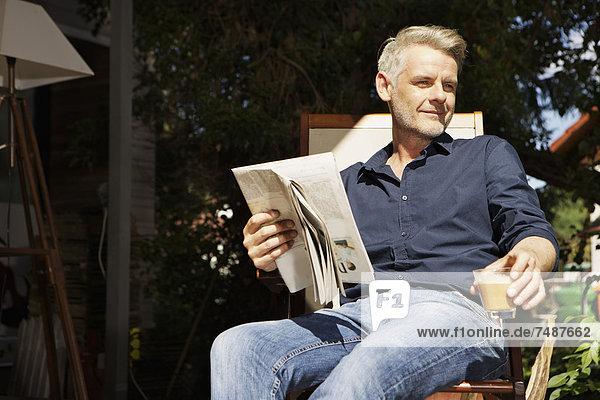Erwachsener Mann auf der Terrasse sitzend und Zeitung lesend
