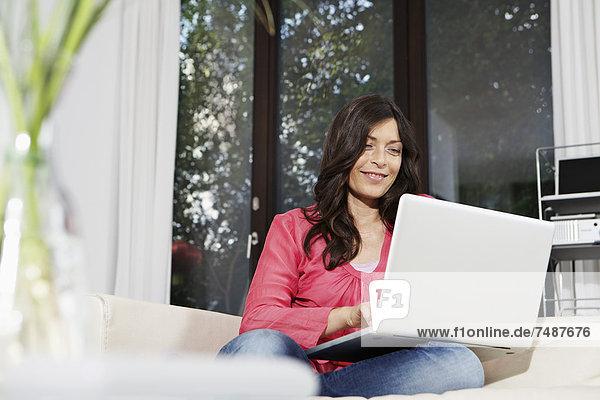 Reife Frau mit Laptop auf dem Sofa  lächelnd  Portrait