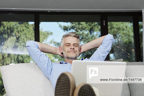 Erwachsener Mann auf dem Sofa sitzend mit Laptop