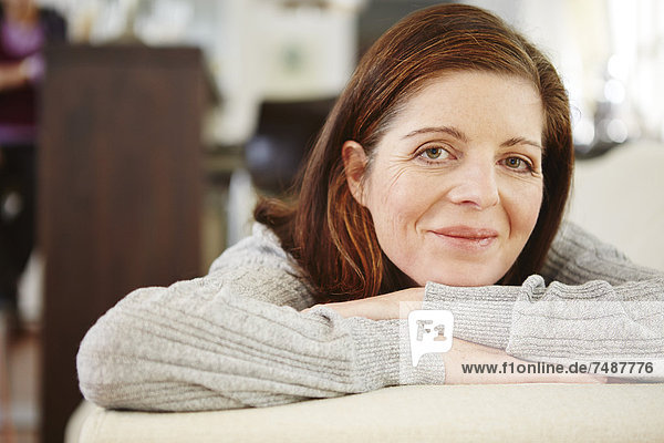 Reife Frau entspannt auf dem Sofa  lächelnd