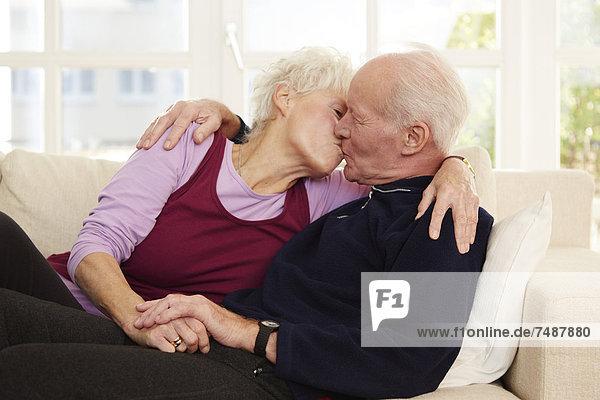 Deutschland  Düsseldorf  Seniorenpaar beim Küssen und Entspannen zu Hause
