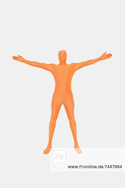 Erwachsener Mann in orangefarbenem Zentai auf weißem Grund stehend