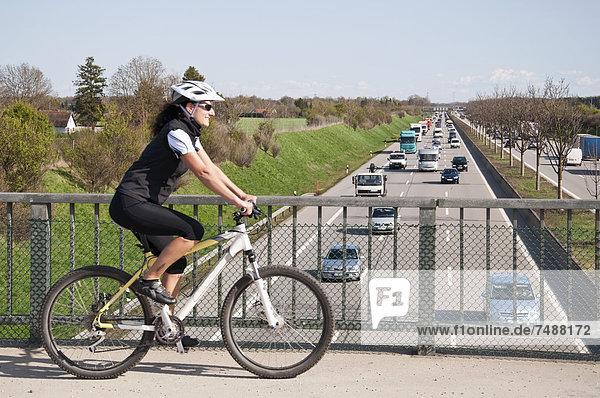 Deutschland  Mittlere erwachsene Frau mit Mountainbike auf Brücke mit Blick auf den Verkehr auf der Autobahn