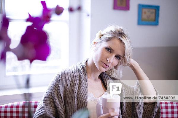 Porträt einer jungen Frau in der Küche mit Kaffee