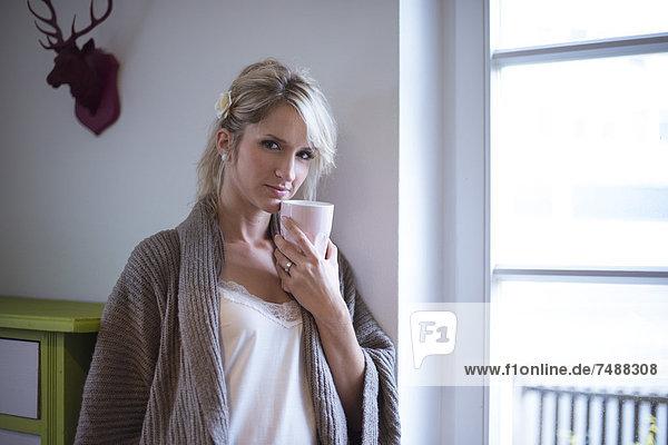 Porträt einer jungen Frau am Fenster stehend mit Kaffee  lächelnd