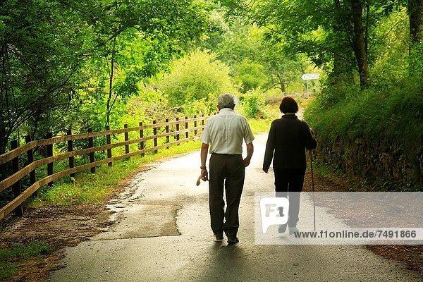 Two adults walking on a country road in Santa Marina Valdeón. Picos de Europa. Leon.