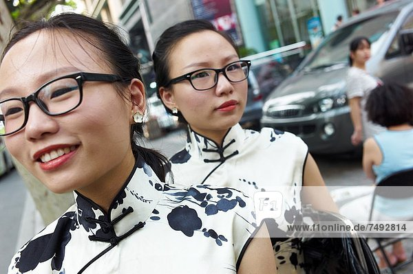 Two twin girls in traditional chinese dresses hailing a taxi cab