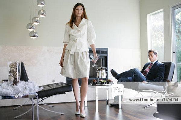 Frau stehend mit einem Martini-Glas  sitzende Mann