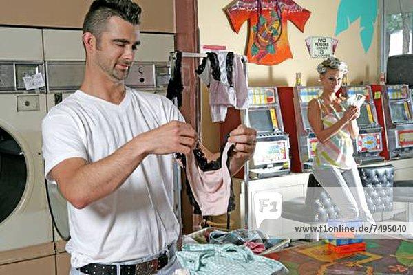 Faltreifen Unterwäsche  Frau zählen Geld in der Nähe von Spielautomaten Mann