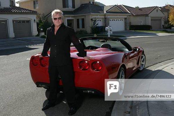 Älterer Mann steht vor eines roten Sportwagens