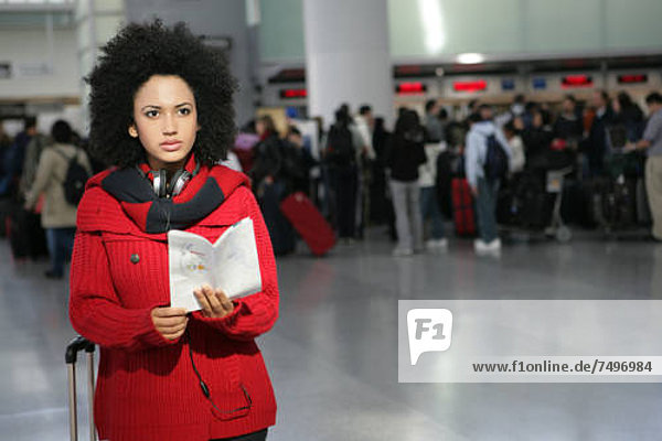 Young African American woman reading pamphlet in airport.