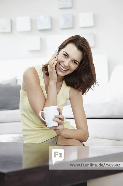 Smiling brunette woman talking on phone