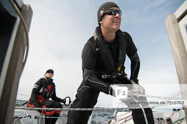 Mann  der das Seil bindet  während die Frau hinten im Segelboot sitzt.