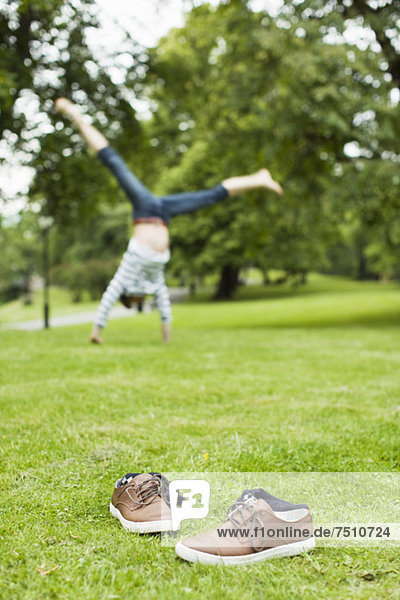 Schuhe und Socken auf Rasen mit Mann  der im Hintergrund im Park Handstand übt.
