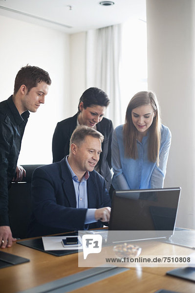 Geschäftskollegen  die Laptop benutzen  während sie im Meeting diskutieren