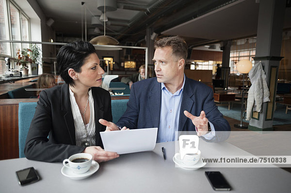 Reife Unternehmerin und Kollegin mit Papierkram am Kaffeetisch