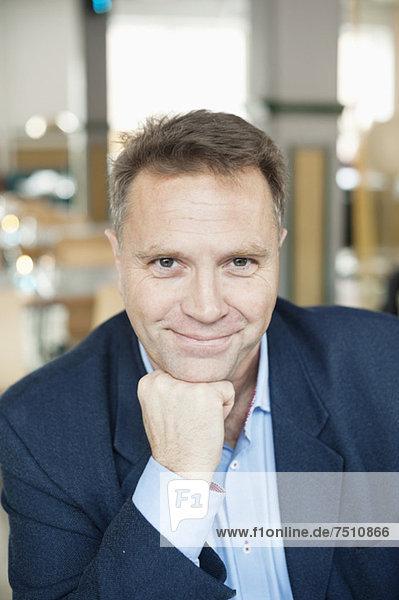 Porträt eines selbstbewussten reifen Geschäftsmannes mit Hand am Kinn