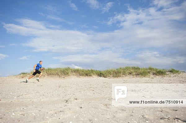 Seitenansicht des jungen Mannes beim Joggen am Strand