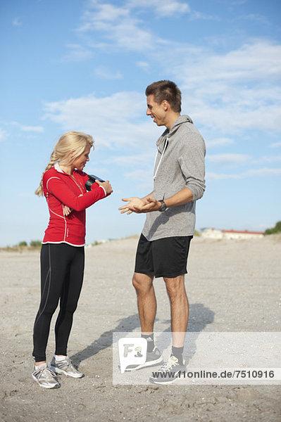 Volle Länge des jungen männlichen Joggers mit weiblichem Freund  der den MP3-Player am Strand anpasst.