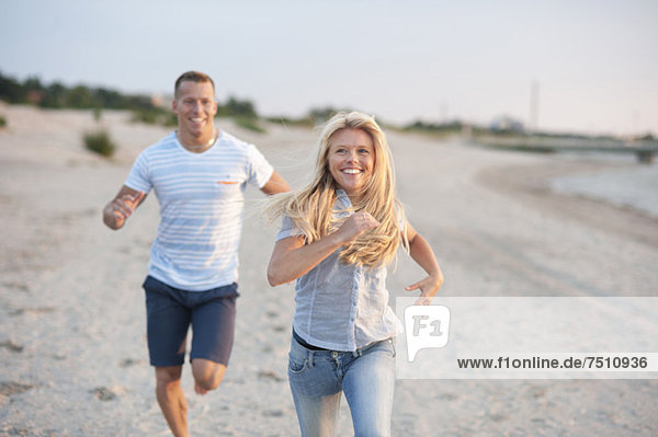 Ein glückliches junges Paar läuft am Strand.