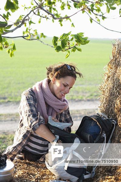 Glückliche junge Wanderin sucht in ihrer Tasche