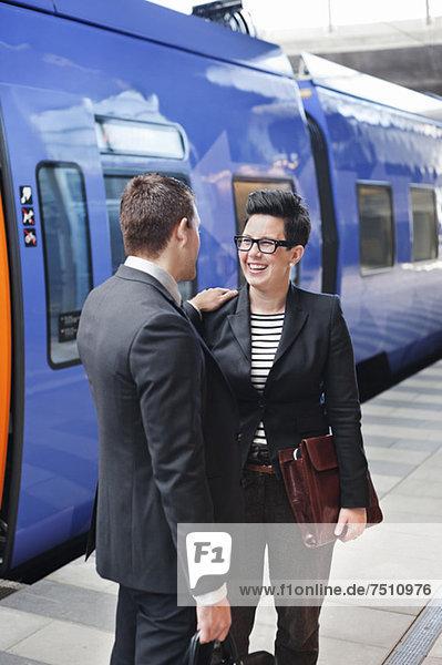 Glückliche Geschäftsleute stehen vor dem Zug auf dem Bahnsteig