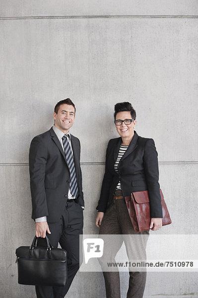 Portrait von glücklichen Geschäftsleuten mit an der Wand stehenden Taschen