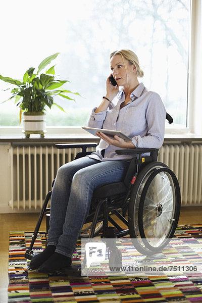 Behinderte Frau mit digitalem Tablett  die zu Hause im Rollstuhl sitzt.
