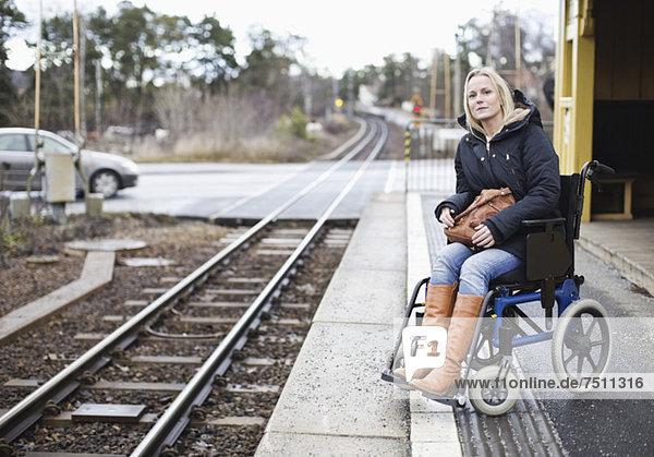 Behinderte Frau im Rollstuhl beim Warten auf den Zug am Bahnhof