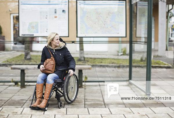 Behinderte Frau im Rollstuhl wartet an der Bushaltestelle
