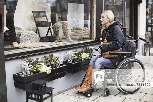 Behinderte Frau im Rollstuhl mit Blick ins Schaufenster
