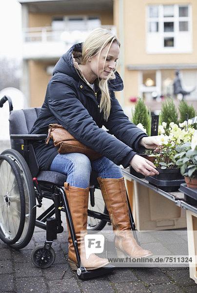 Behinderte Frau im Rollstuhl bei der Pflanzenwahl im Gartencenter