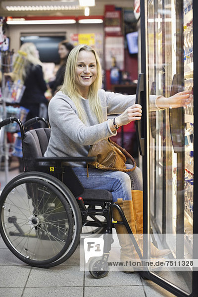 Portrait of happy disabled woman in wheelchair at refrigerated section of supermarket