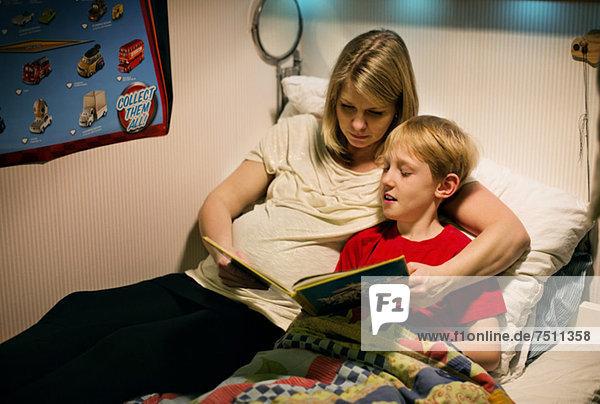 Mittlere erwachsene Frau liest Buch mit ihrem Sohn im Bett