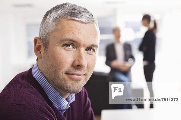 Porträt eines reifen Geschäftsmannes  der mit Kollegen im Hintergrund lächelt