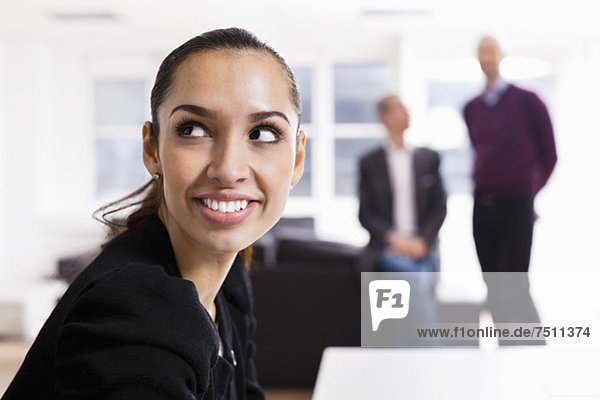 Glückliche Geschäftsfrau schaut mit Kollegen im Hintergrund weg