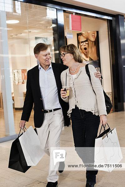 Fröhliches Seniorenpaar mit Einkaufstaschen im Einkaufszentrum