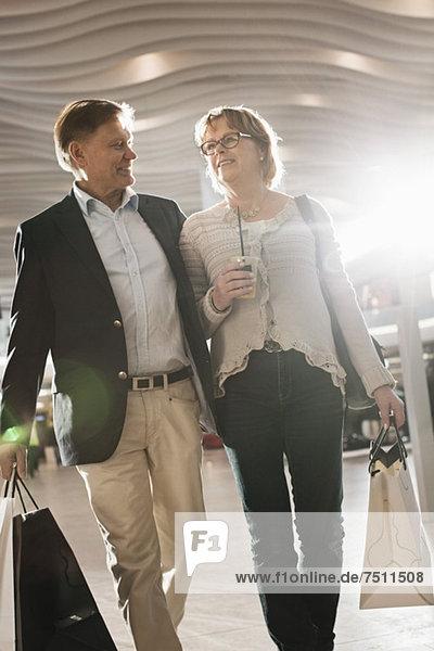 Glückliches Seniorenpaar mit Einkaufstaschen im Einkaufszentrum