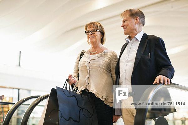 Glückliches Seniorenpaar mit Taschen auf einer Rolltreppe im Einkaufszentrum